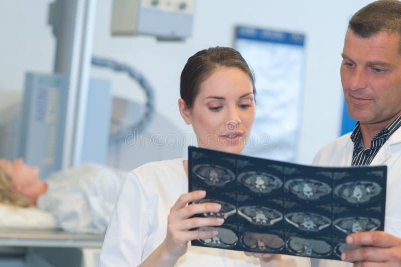 Läkare som talar med ligan om röntgen hos patienter arkivbild