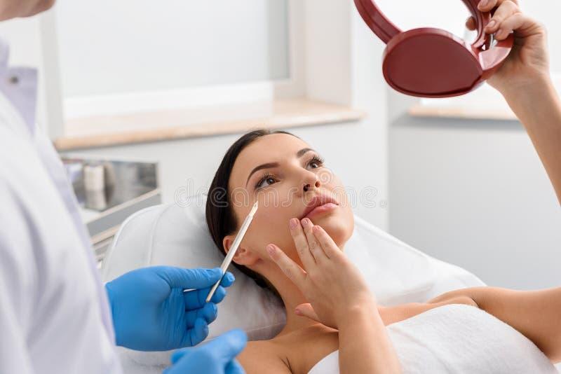 Läkare som visar problem-benägen hud av kvinnan royaltyfria foton