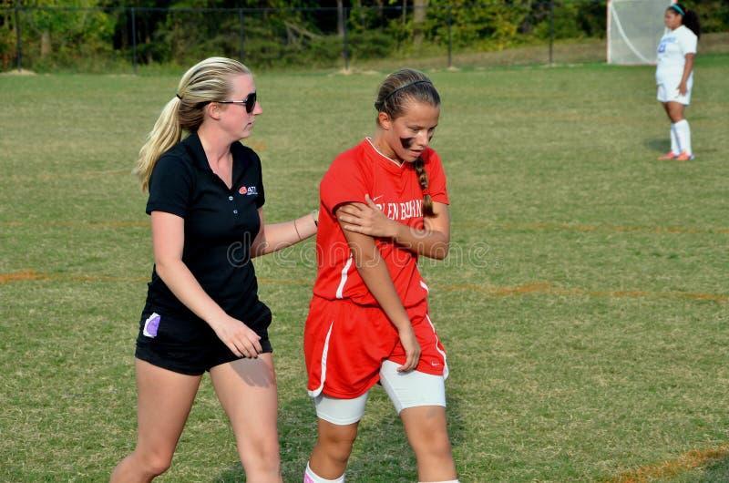 Läkaren hjälper en fotbollspelare att gå till sidlinjer, når han har fått sårad arkivfoton
