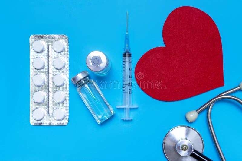 Läkarundersökning, medicinstetoskop, injektionsspruta, injektion och preventivpillerar på blå bakgrund Hälsovård eller sjukdom Ka arkivfoto