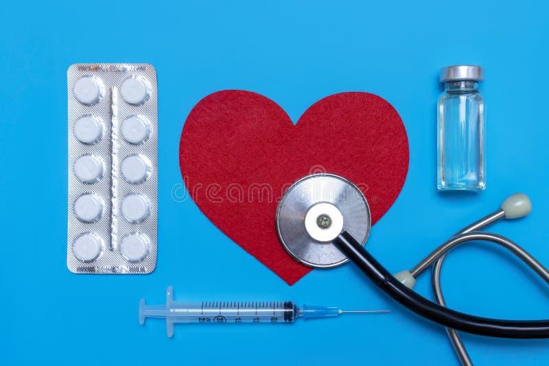 Läkarundersökning, medicinstetoskop, injektionsspruta, injektion och preventivpillerar på blå bakgrund Hälsovård eller sjukdom Ka arkivbilder