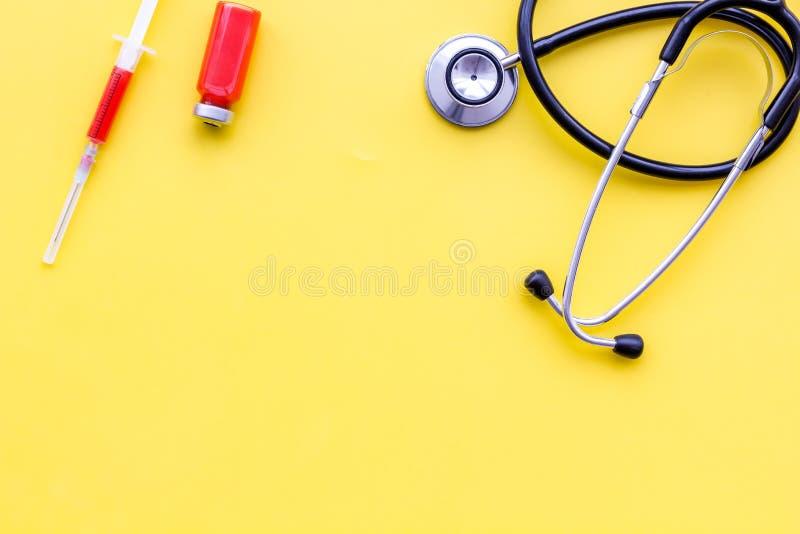 Läkarundersökning- och behandlingbegrepp Stetoskop injektionsspruta på gult utrymme för kopia för bästa sikt för bakgrund royaltyfria bilder