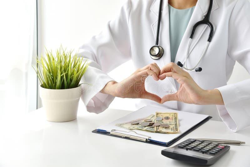 Läkarundersökning- och sjukförsäkringbegrepp, doktor som gör gest för handhjärtaform med pengar i sjukhusbakgrund arkivfoto