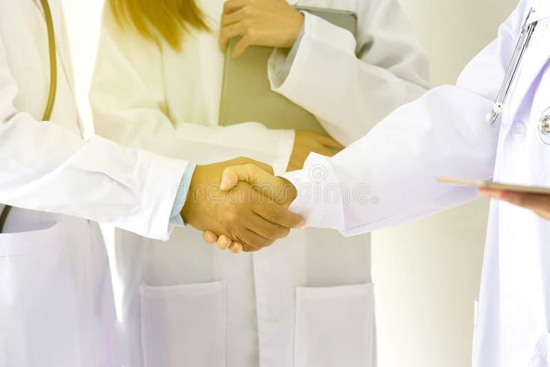 Läkarundersökning- och sjukvårdbegrepp Ung medicinsk folkhandshaking på sjukhuset Laget manipulerar arbete på kontoret E arkivbilder
