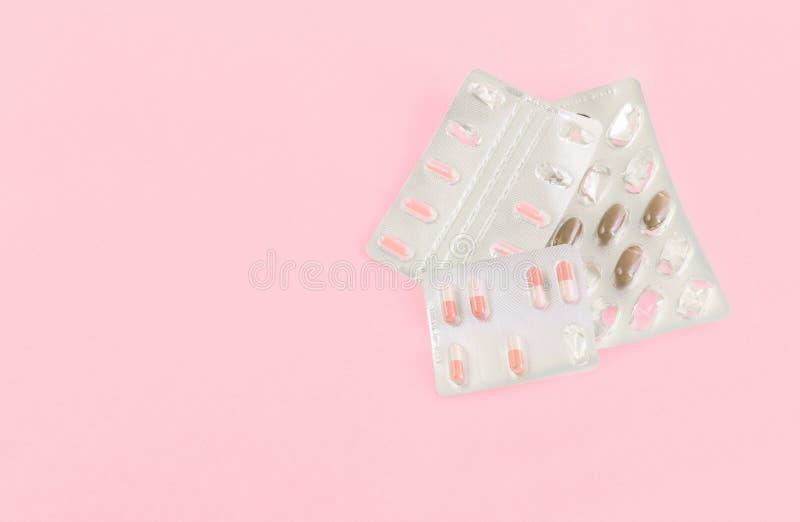 Läkemedel, kapslar på rosa bakgrund Läkemedelsbegrepp Läkemedel för behandling av sjukdomar, virus, höstkyla royaltyfri foto