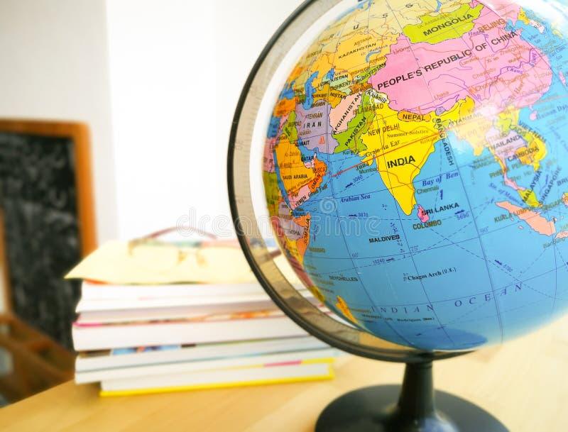 Länder und Kontinente schließen oben mit der Farbkarte auf einer Kugel mit Büchern im Hintergrund lizenzfreies stockfoto