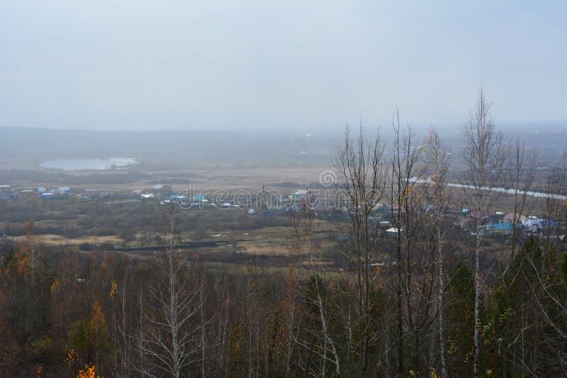 Ländliche Herbstlandschaft in Russland am bewölkten und nebeligen Tag Ansicht über Dorf und Fluss durch Bäume stockbilder