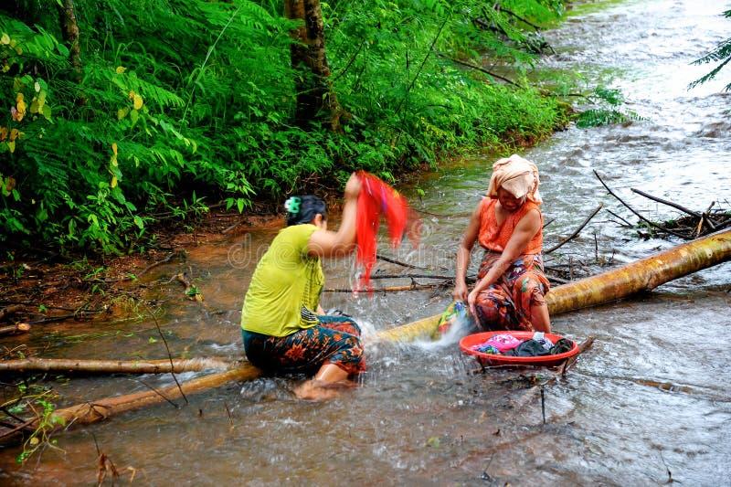 Ländliche housewifes, die Kleidung auf traditionelle Art auf flachem r waschen stockbild