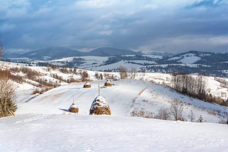 Ländliche Landschaft des Winters, Heuschober auf dem Hintergrund von Schnee-mit einer Kappe bedeckten Bergen lizenzfreie stockbilder