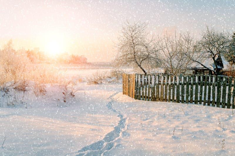 Ländliche Landschaft des Winters im zeit- Winterdorf des sonnigen Sonnenuntergangs unter schneebedeckten Bäumen unter Schneefälle lizenzfreie stockbilder