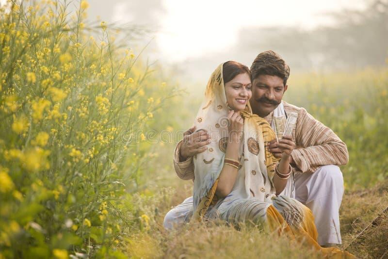 Ländliche Paare, die Anmerkungen der indischen Rupie auf dem Landwirtschaftsgebiet halten stockfoto