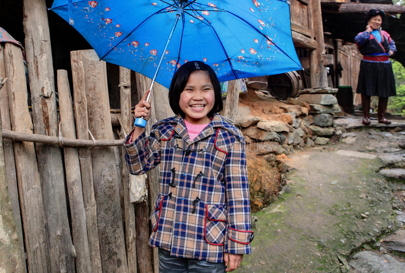 Ländliches asiatisches Mädchen, ungefähr 8 Jahre, versteckender blauer Regenschirm und Lachen stockfoto