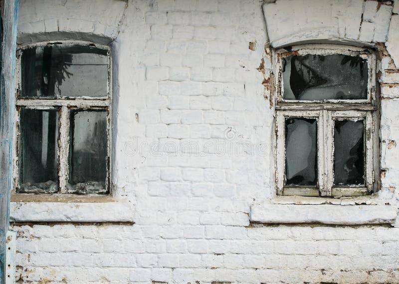 ländliches Haus der Backsteinmauer mit zwei kleines altes gebrechliches Windows stockfoto