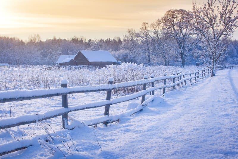 Ländliches Haus mit einem Zaun im Winter lizenzfreie stockfotos