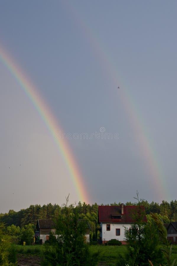 Ländliches Polen, Ilawa-Region, Regenbogen über Dorf von Sapy lizenzfreies stockbild