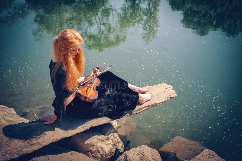 Ländliches rothaariges Mädchen mit einer Violine stockfotos