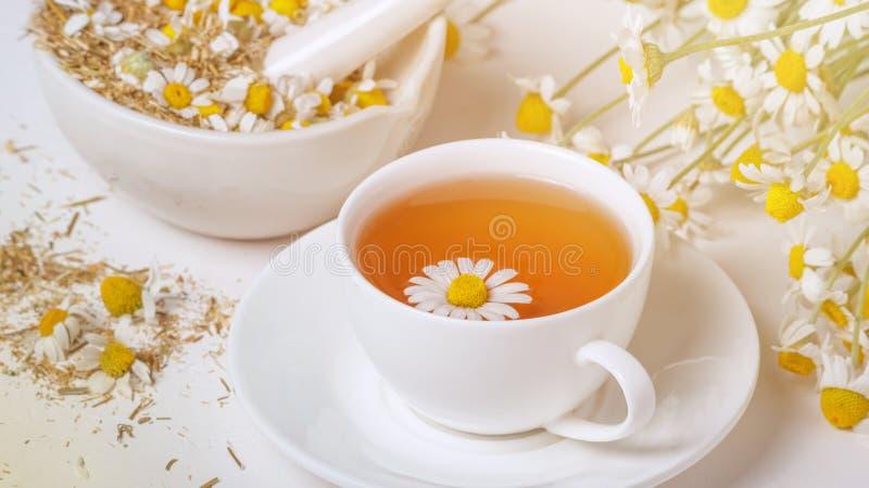 Ländliches Stillleben - Schale gebrauter Kamillentee auf dem Hintergrund eines Blumenstraußes der Gänseblümchen stockbild