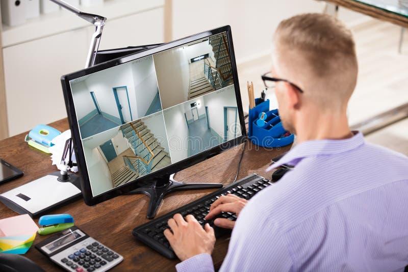 Längd i fot räknat för affärsmanLooking At CCTV på datoren arkivfoton