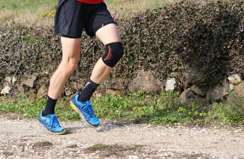 Längdlöpninglöpare under loppet med hans knä som slås in av a arkivbild