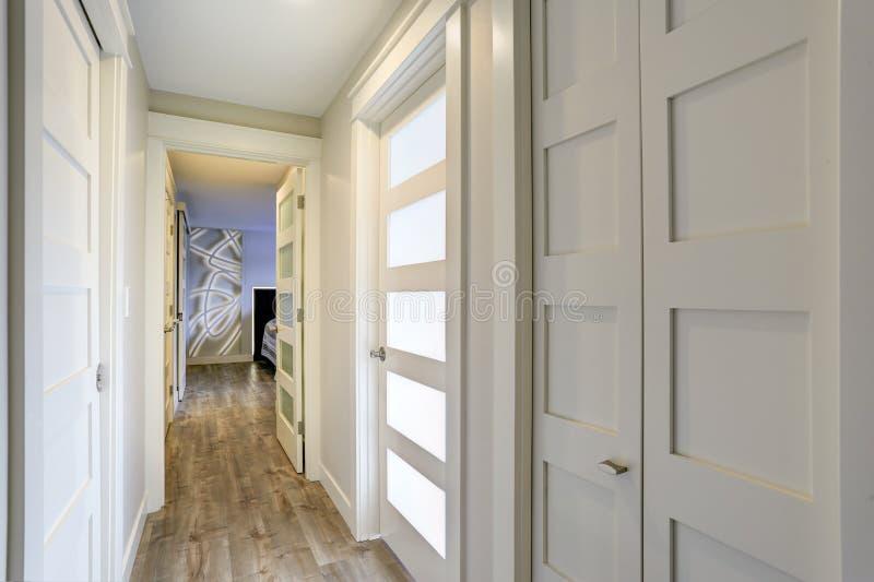 Länge betonade den smala korridoren med vita dörrar med glass paneler arkivbild