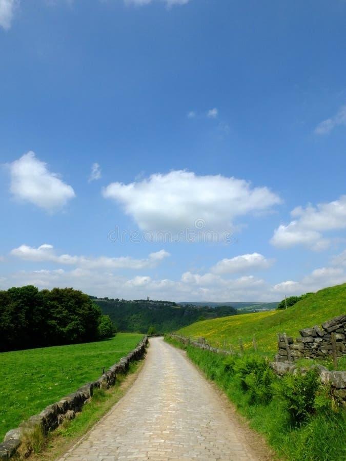 Länge lappat köra för stenstenväg som är sluttande i härlig yorkshire dalbygd med gröna sommarängar arkivfoto