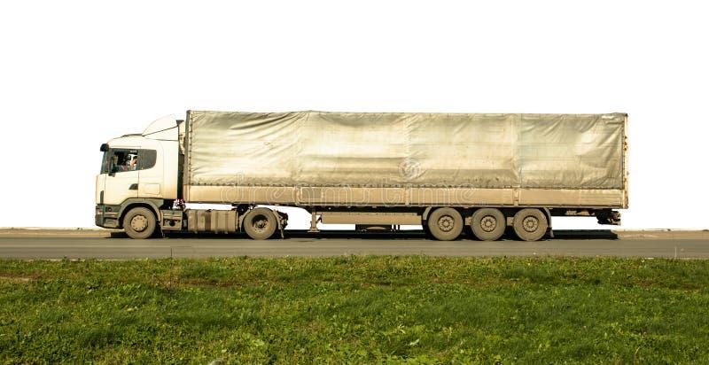 Länge smutsig skåpbillastbil på isolerad vit för grönt gräs för asfaltväg royaltyfri fotografi