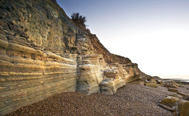 längs härliga klippor striated soluppgång i lager arkivbild