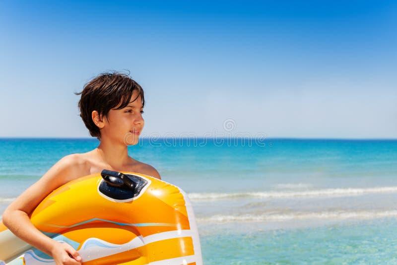 Längtande pojkestående mot härlig seascape under semestrar royaltyfri fotografi