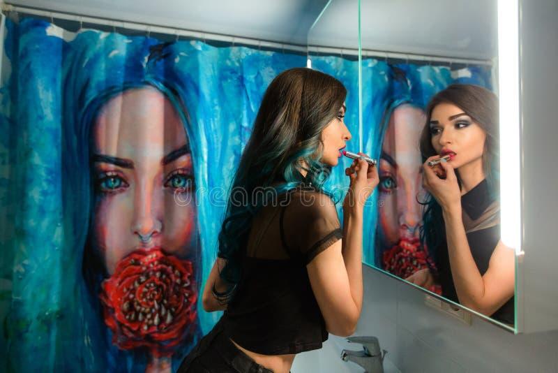 Läppstift för rouge för nätt ung kvinna röd framme av hennes badrumspegel Hårpermanent Duschgardiner med konstmålning arkivbild