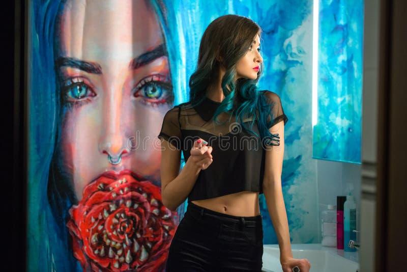 Läppstift för rouge för nätt ung kvinna röd framme av hennes badrumspegel Hårpermanent Duschgardiner med konstmålning royaltyfri fotografi