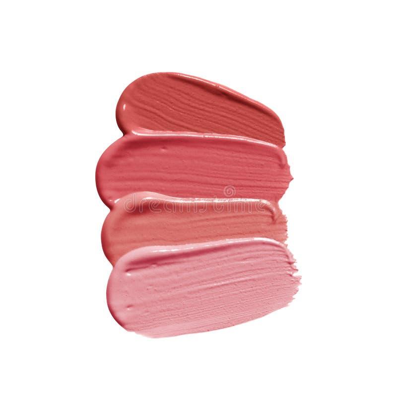 Läppstiftborsteslaglängder i olika skuggor av rosa näck färg Makeupprovkartafläck som isoleras på vit bakgrund kosmetisk produkt royaltyfri fotografi