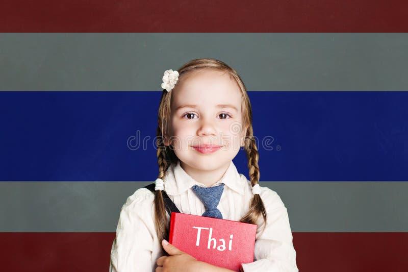 Lär det thailändska språket Thailand begrepp med ungeliten flickastudenten med den röda boken mot den Thailand flaggabakgrunden fotografering för bildbyråer