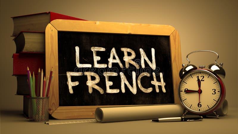Lär franska - Motivational citationstecken på den svart tavlan fotografering för bildbyråer