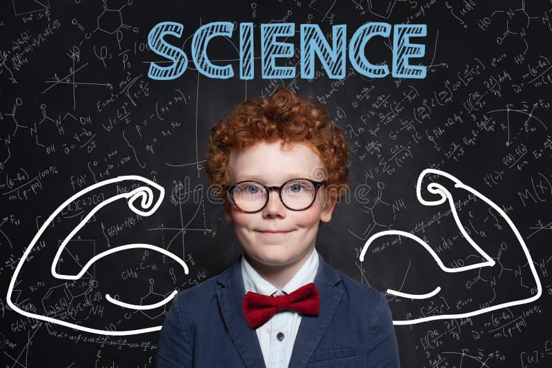 Lär vetenskap Stark smart barnstudent på svart tavlabakgrund med formler royaltyfria foton
