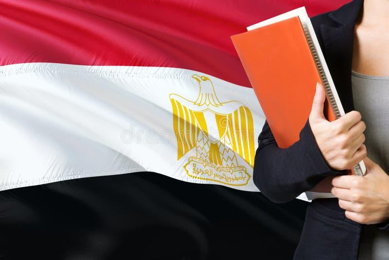 Lära egyptiskt språkbegrepp Anseende för ung kvinna med den Egypten flaggan i bakgrunden Lärare som rymmer böcker, apelsin arkivbilder