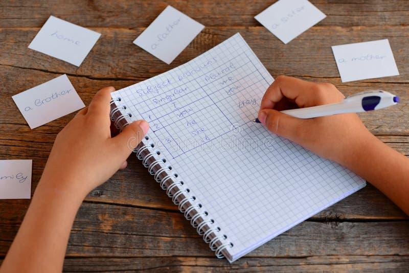 Lära engelskt språk En liten unge skriver ämnespronomen En anteckningsbok, en penna, kort med ord på en trätabell fotografering för bildbyråer