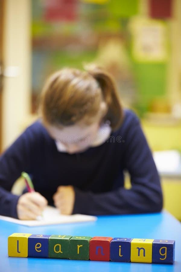 Lära för ord som stavas i träkvarter med eleven bakom arkivbild