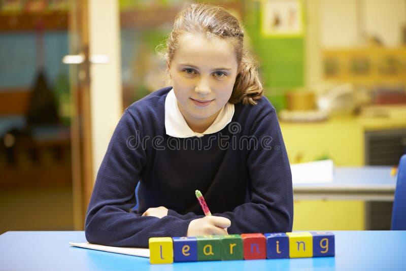 Lära för ord som stavas i träkvarter med eleven bakom fotografering för bildbyråer