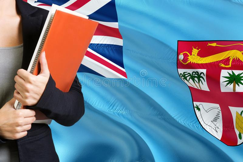Lära Fijian språkbegrepp Anseende för ung kvinna med den fijianska flaggan i bakgrunden L?rare som rymmer b?cker, orange mellanru royaltyfria foton