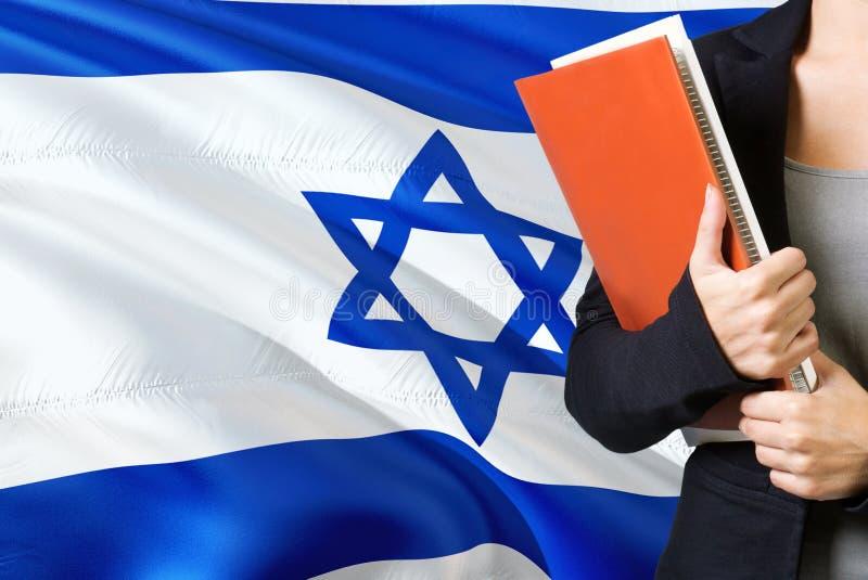 Lära israeliskt språkbegrepp Anseende för ung kvinna med den Israel flaggan i bakgrunden Lärare som rymmer böcker, apelsin fotografering för bildbyråer