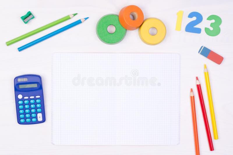 lära maths Lura skrivbordet för ` s med den tomma anteckningsboken, färgrika blyertspennor, nummer och en räknemaskin arkivbild