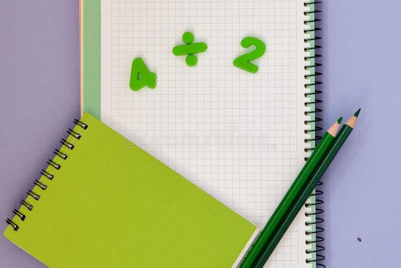 lära maths Lura skrivbordet för ` s med den tomma anteckningsboken, färgrika blyertspennor och bästa sikt för nummer med kopierin arkivbilder