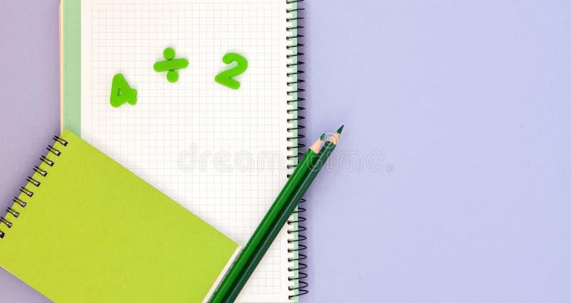 lära maths Lura skrivbordet för ` s med den tomma anteckningsboken, färgrika blyertspennor och bästa sikt för nummer med kopierin arkivbild