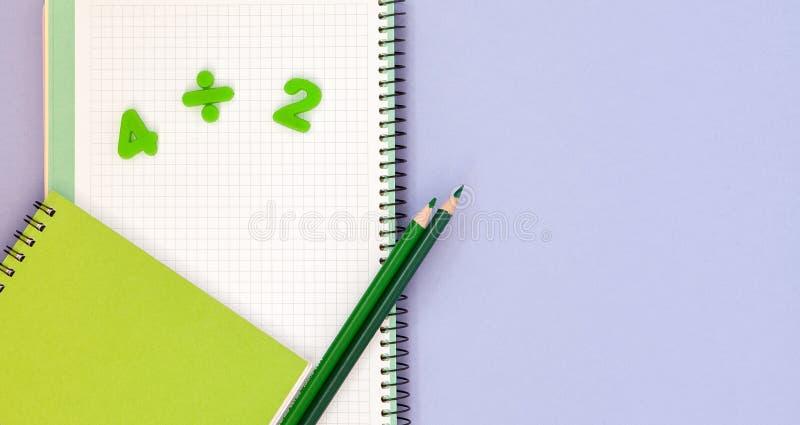 lära maths Lura skrivbordet för ` s med den tomma anteckningsboken, färgrika blyertspennor och bästa sikt för nummer med kopierin arkivfoto
