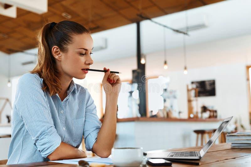 Lära och att studera Kvinna som använder bärbar datordatoren på kafét som arbetar arkivfoton