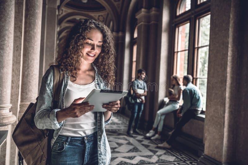 lära online Härlig kvinnlig student som förbereder sig till kurser på den digitala minnestavlan royaltyfri fotografi