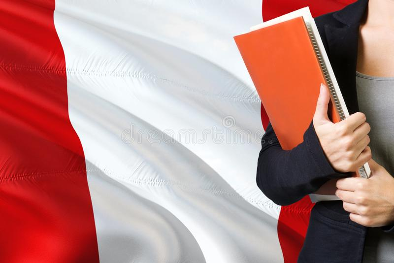 Lära peruanskt språkbegrepp Anseende för ung kvinna med den Peru flaggan i bakgrunden L?rare som rymmer b?cker, orange mellanrum arkivbild