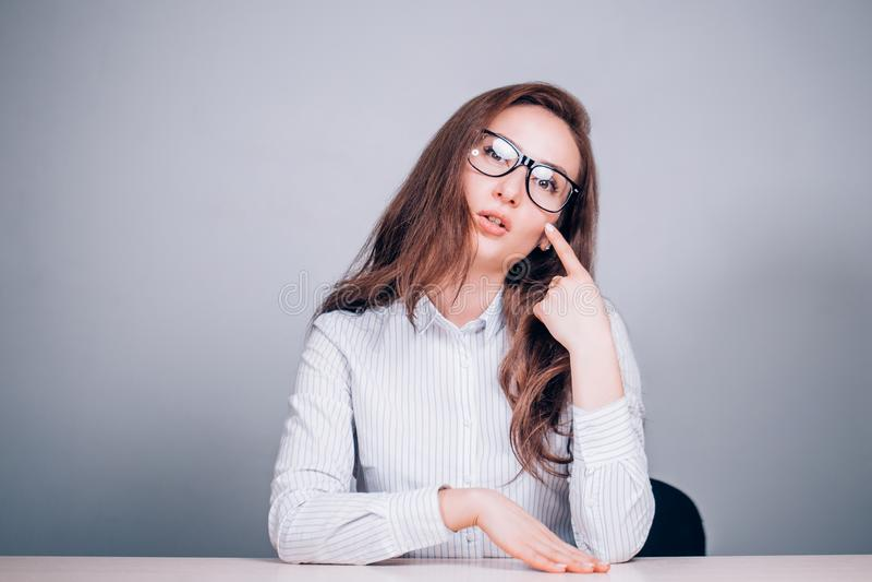 Lärare eller affärskvinna med exponeringsglas som sitter på tabellen royaltyfria foton