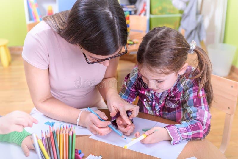 Lärare Harnessing Kids Creativity i dagiset och förträningen royaltyfria foton