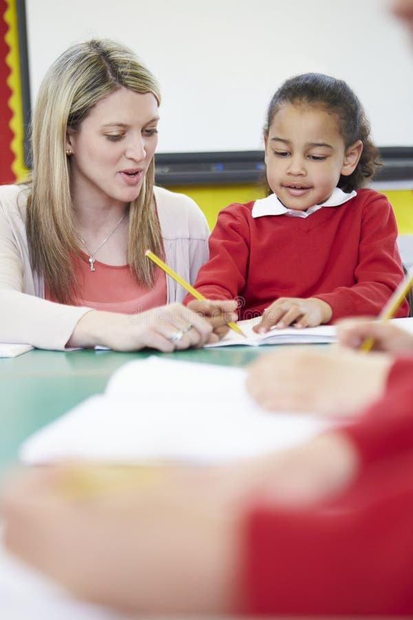Lärare Helping Female Pupil med handstilläsning på skrivbordet royaltyfria bilder